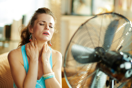 relaxed young woman in the modern living room in sunny hot summer day cooling down in the front of fan suffering from summer heat.