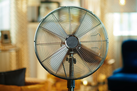 Closeup on electric floor standing fan at modern home in sunny hot summer day.