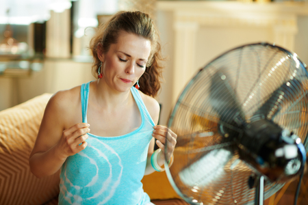 sweating woman at modern home in sunny hot summer day cooling down using electric floor standing fan suffering from summer heat.