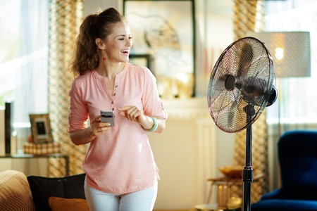 happy modern housewife in the modern house in sunny hot summer day using smart home app in smartphone to control fan.