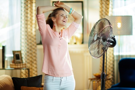 smiling young woman at modern home in sunny hot summer day enjoying breeze in the front of fan.