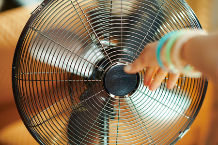 working metallic floor standing fan and female hand stretching to fan in the modern living room in sunny hot summer day. Standard-Bild