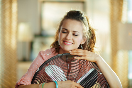 relaxed young woman in the modern house in sunny hot summer day embracing electric metallic fan.
