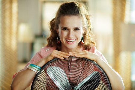 Ritratto di sorridente casalinga elegante con ventilatore da pavimento metallico nel moderno soggiorno in una calda giornata estiva di sole. Archivio Fotografico