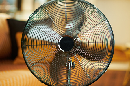 Closeup on working metallic floor standing fan at modern home in sunny hot summer day. 版權商用圖片