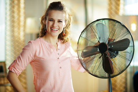 smiling elegant woman in the modern living room in sunny hot summer day near electric floor standing fan. Banco de Imagens