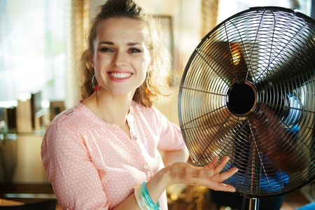 happy young housewife in the modern house in sunny hot summer day showing metallic floor standing fan.