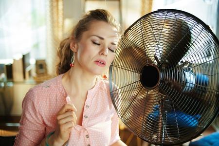 trieste jonge vrouw in de moderne woonkamer op zonnige warme zomerdag genietend van een briesje aan de voorkant van een werkende ventilator die lijdt aan zomerse hitte.