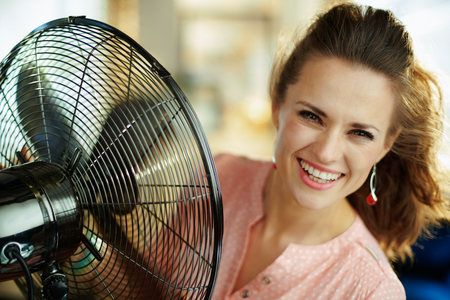 Portrait of smiling young housewife at modern home in sunny hot summer day cooling down using electric metallic fan. Stock Photo