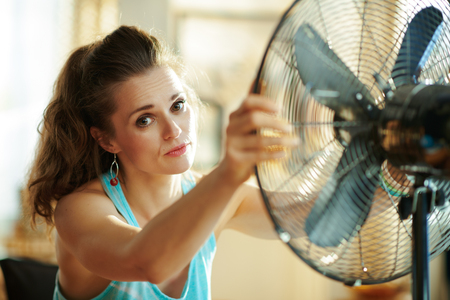 Portrait of woman in the modern living room in sunny hot summer day enjoying fresh air in the front of working fan suffering from summer heat. Stok Fotoğraf