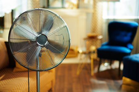 Closeup on working electric floor standing fan in the modern house in sunny hot summer day.