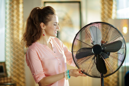 smiling stylish housewife in the modern living room in sunny hot summer day near electric metallic fan.
