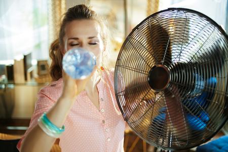 young housewife at modern home in sunny hot summer day cooling down in the front of fan and drinking cold water.