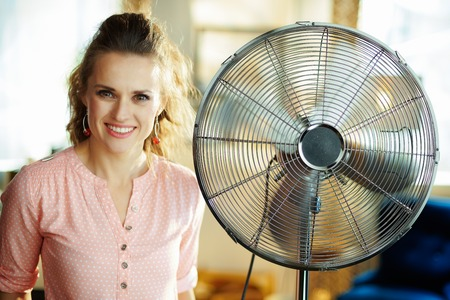 Portrait of happy elegant woman in the modern living room in sunny hot summer day near metallic floor standing fan. Stock Photo