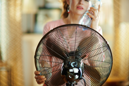 Closeup on relaxed young housewife with bottle of cold water using electric floor standing fan in the modern house in sunny hot summer day.