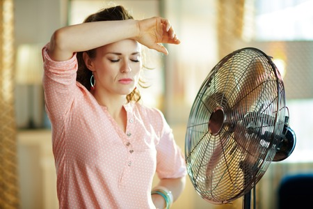 sad stylish housewife in the modern living room in sunny hot summer day exhausted from summer heat while standing in the front of fan.