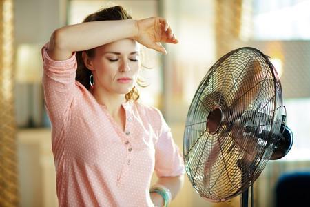 Traurige stilvolle Hausfrau im modernen Wohnzimmer an sonnigen heißen Sommertagen, die von der Sommerhitze erschöpft sind, während sie vor dem Ventilator steht. Standard-Bild