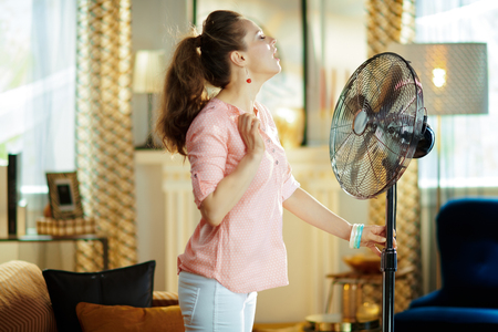 relaxed stylish woman in the modern living room in sunny hot summer day cooling down in the front of fan.