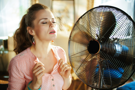 sweating elegant woman in the modern house in sunny hot summer day enjoying freshness in the front of fan suffering from summer heat.