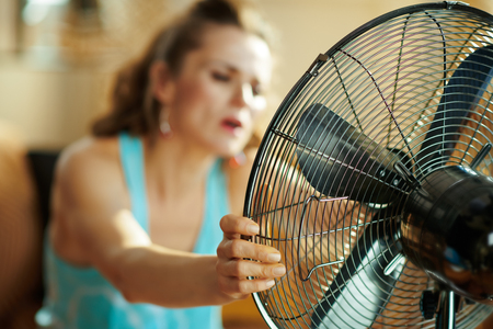 Closeup on hot modern housewife in the modern living room in sunny hot summer day using electric metallic fan suffering from summer heat. Standard-Bild - 124770014
