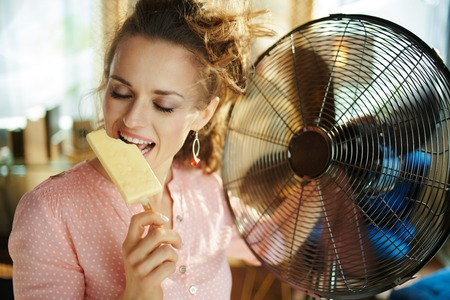 happy stylish woman in the modern house in sunny hot summer day using electric metallic fan while eating ice cream.