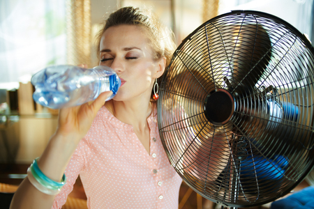 elegant woman in the modern living room in sunny hot summer day enjoying breeze in the front of working fan and drinking cold water. Stock Photo
