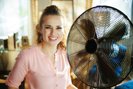 Portrait of smiling elegant woman at modern home in sunny hot summer day cooling down using electric metallic fan.