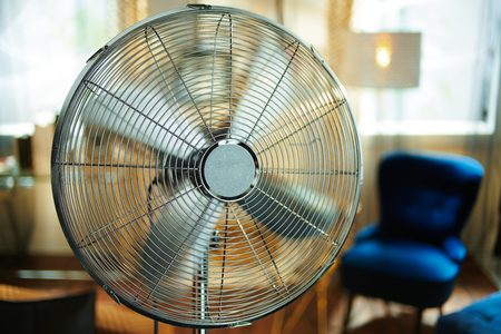 Closeup on working electric floor standing fan in the modern house in sunny hot summer day. Stok Fotoğraf - 124770585