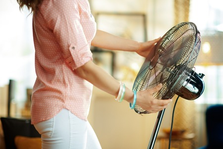 Closeup on stylish woman at modern home in sunny hot summer day enjoying freshness in the front of fan. Stok Fotoğraf