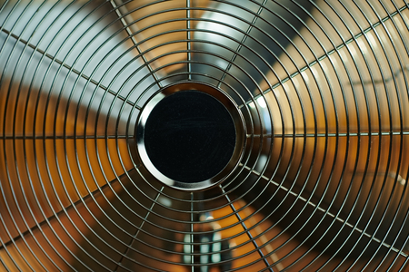 Closeup on electric metallic fan in the modern house in sunny hot summer day. Stok Fotoğraf
