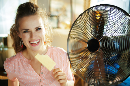 happy stylish woman with ice cream cooling down in the front of fan at modern home in sunny hot summer day. Standard-Bild - 124770592