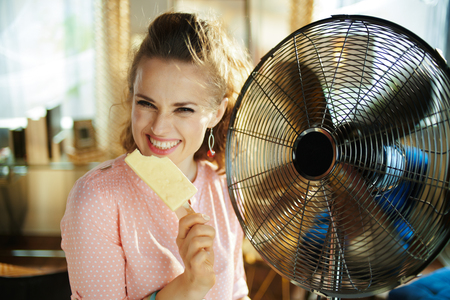 happy stylish woman with ice cream cooling down using electric metallic fan in the modern house in sunny hot summer day. Standard-Bild - 124758478