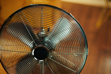 Closeup on working electric metallic fan at modern home in sunny hot summer day.