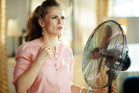 sweating young housewife at modern home in sunny hot summer day suffering from summer heat while standing in the front of fan. Standard-Bild - 124758486