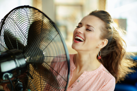 smiling stylish housewife in the modern house in sunny hot summer day using electric floor standing fan.