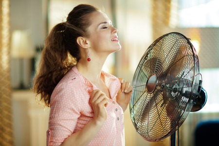 relaxed modern woman in the modern living room in sunny hot summer day cooling down using electric metallic fan.