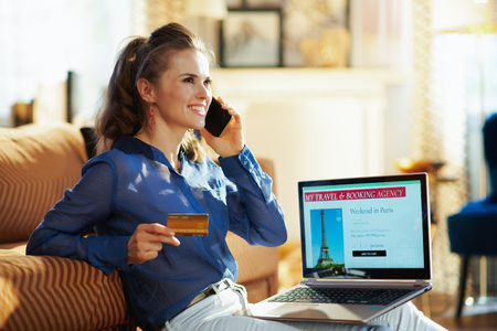 happy young woman with opened on laptop online travel & booking agency site holding gold credit card talking on a mobile phone at modern home in sunny summer day. Banque d'images - 124760775