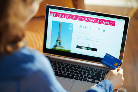 Seen from above young woman with opened on laptop online travel & booking agency site holding blue credit card at modern home in sunny summer day. A fake website is made for illustrative purposes. Banque d'images - 124764161