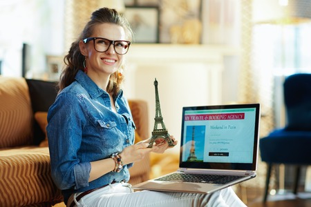 happy modern woman with opened on laptop online travel & booking agency site holding a souvenir of the eiffel tower in the modern house in sunny summer day.