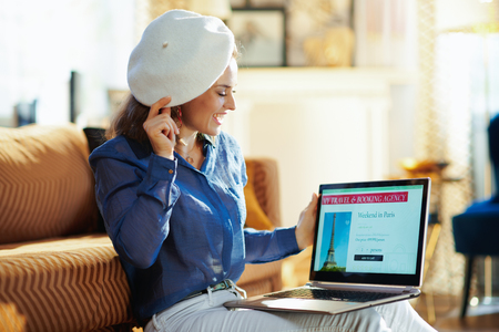 smiling stylish woman with opened on laptop online travel & booking agency site wearing white beret in the modern house in sunny summer day. A fake website is made for illustrative purposes.