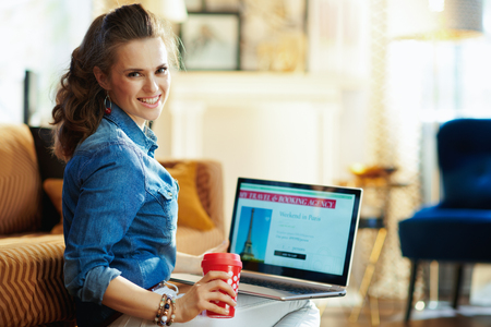 smiling young woman with red coffee cup and opened on laptop online travel & booking agency site in the modern house in sunny summer day. A fake website is made for illustrative purposes.