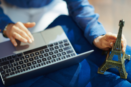 Closeup on modern woman holding a souvenir of the eiffel tower with laptop at modern home in sunny summer day. A fake website is made for illustrative purposes. Stock Photo