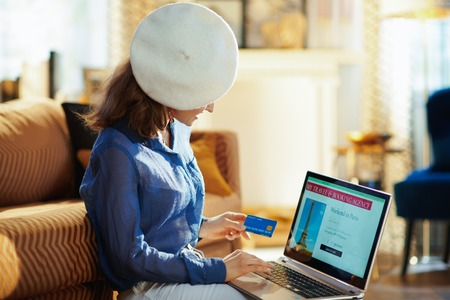 stylish woman in white beret with credit card ordering a trip to paris on laptop using online travel & booking agency site at modern home in sunny summer day. Stockfoto