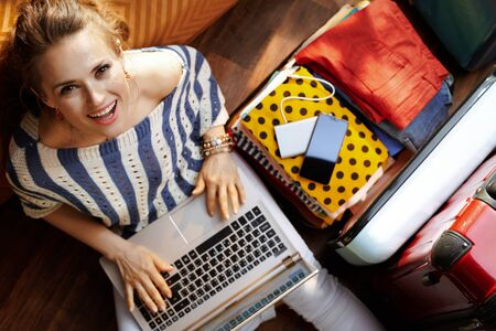 Upper view of happy elegant woman in white pants and striped blouse in the modern house in sunny summer day booking hotel online near open travel suitcase. Stok Fotoğraf