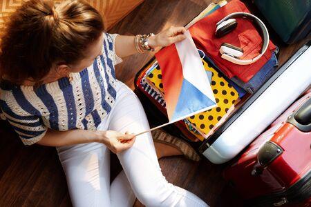 Upper view of modern woman in white pants and striped blouse with Czech flag near open travel suitcase in the modern living room in sunny summer day. 版權商用圖片 - 124770596