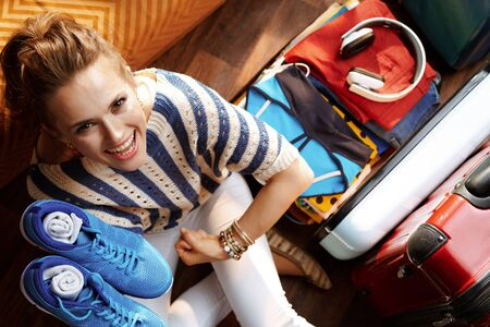 Upper view of happy stylish woman in striped blouse at modern home in sunny summer day showing biceps while packing fitness gear near open travel suitcase to stay fit while having summer holidays. Stok Fotoğraf - 124770597