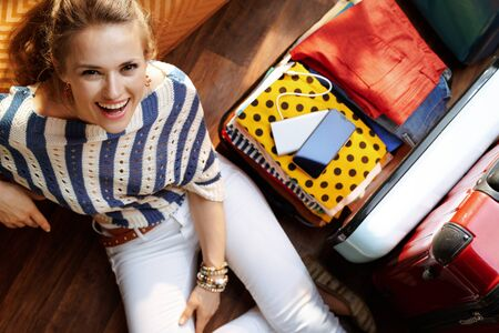 Upper view of smiling elegant woman in white pants and striped blouse sitting near open travel suitcase in the modern living room in sunny summer day. Stock Photo