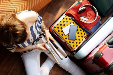Upper view of stylish woman in white pants and striped blouse at modern home in sunny summer day packing hair curler and iron in open travel suitcase. Stok Fotoğraf - 124773743