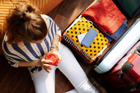 Upper view of elegant woman in white pants and striped blouse with coffee cup near open travel suitcase at modern home in sunny summer day.