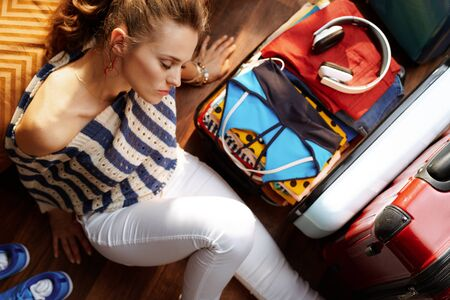 Upper view of relaxed modern woman in white pants and striped blouse in the modern house in sunny summer day near open travel suitcase. Stok Fotoğraf - 124773745